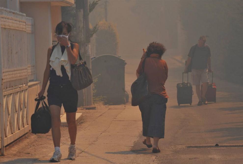 10) Жители Агиос Стефанос – северного пригорода Афин – покидают свои дома, окруженные крупными лесными пожарами, недалеко от столицы Греции в воскресенье. Тысячи людей были эвакуированы, так как гонимые ветром пожары уничтожают дома и угрожают нескольким жилым районам. (Nikolas Giakoumidis/AP)