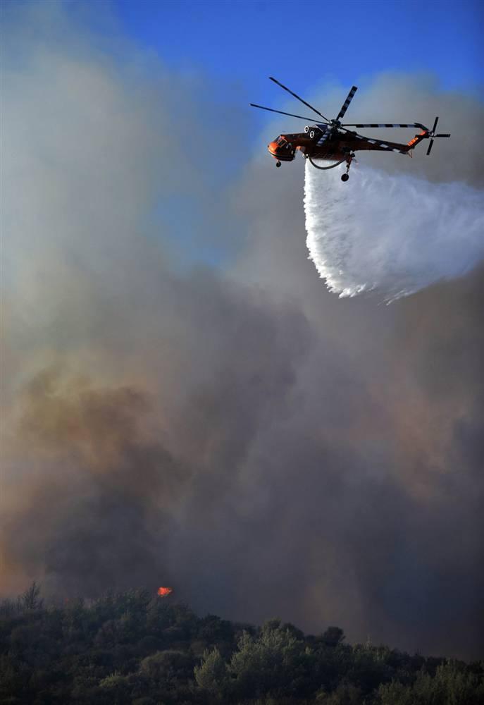 9) Пожарный вертолет сбрасывает воду на горящий лес в Агиос Стефанос в воскресенье.  (Nikolas Giakoumidis/AP)