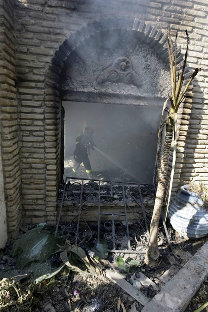6) Пожарный тушит дом изнутри в Марафоне к северу от Афин в воскресенье. (Icon/Reuters)
