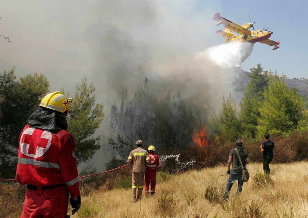 1) Самолет с водой летит над Диони в 12 км к северу от Афин, Греция, в понедельник 24 августа. Добровольцы и пожарные продолжают сражаться с бушующими лесными пожарами, приближающимися к Афинам третий день подряд. (Orestis Panagiotou/EPA)