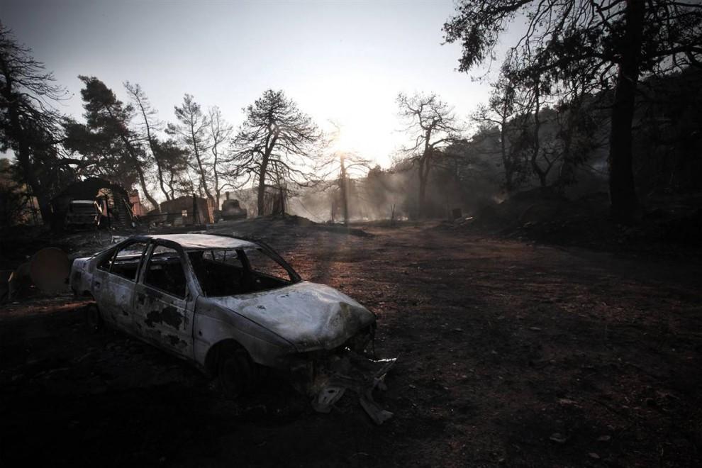 2) Сожженный автомобиль в Агиос Стефанос в понедельник. Пожарные и самолеты вступили сегодня в битву с лесными пожарами, рвущимися к Афинам, по просьбе напуганных жителей. (Angelos Tzortzinis/AFP - Getty Images)