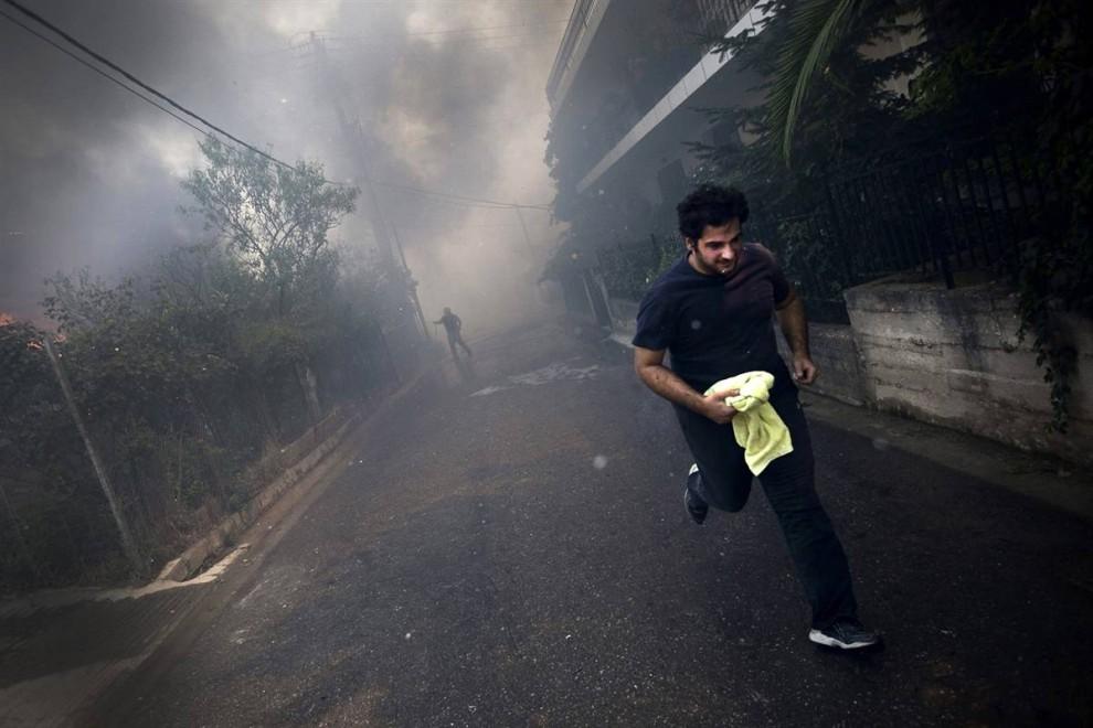 3) Человек убегает от пожара в Агиос Стефанос в воскресенье. Пожарные и местные жители приложили огромные усилия, чтобы сдержать сильнейший пожар в восточном пригороде Афин, который прожег плешь в 30 км в одном из лесов недалеко от столицы. (Angelos Tzortzinis/AFP - Getty Images)