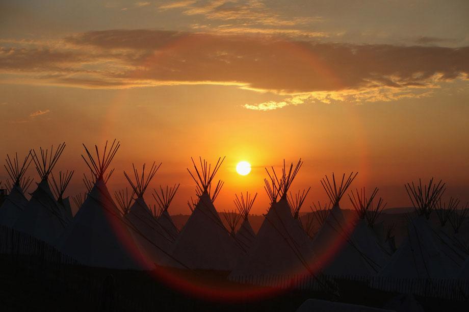33) Солнце садится над полем с типи, в то время как музыкальные фанаты начинают прибывать на площадку фестиваля Гластонбери 24 июня 2009 года в Гластонбери, английское графство Сомерсет. Ворота были открыты для первых из 140 тысяч музыкальных фанатов, прибывающих на однин из крупнейших в Европе музыкальных фестивалей. (Photo by Matt Cardy/Getty Images)