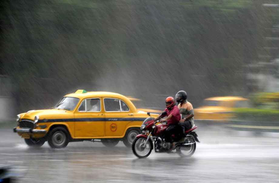 46) Индийский мотоциклист с пассажиром едут рядом с желтыми такси во время муссонного дождя в Калькутте 30 июня 2009. Несмотря на долгий зной в июне и задержку начала сезона муссонов, сильные дожди все-таки начали идти в некоторых районах на севере и востоке Индии. (DESHAKALYAN CHOWDHURY/AFP/Getty Images)