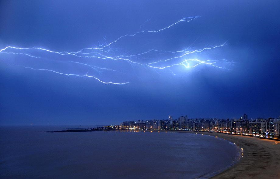 34) Молния освещает ночное небо Монтевидео, во время грозы над уругвайской столицей 5 июля 2009. (MARIANA SUAREZ/AFP/Getty Images)
