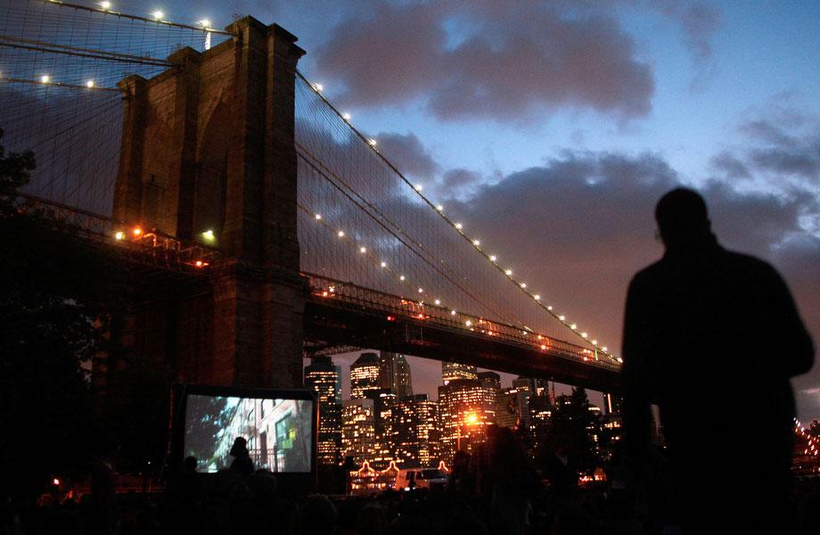 35) Многочисленная аудитория смотрит презентацию, сидя на траве в парке под Бруклинским мостом. На фоне, на горизонте видны небоскребы Манхэттена. Снимок сделан во время кинопоказа на улице 9 июля 2009 года в Нью-Йорке. Просмотр фильмов под открытым небом – обычный для нью-йоркцев способ проводить свой летний досуг. Во время теплых месяцев года в разных районах Нью-Йорка проводятся показы и фестивали кино под открытым небом. (Photo by Chris Hondros/Getty Images)