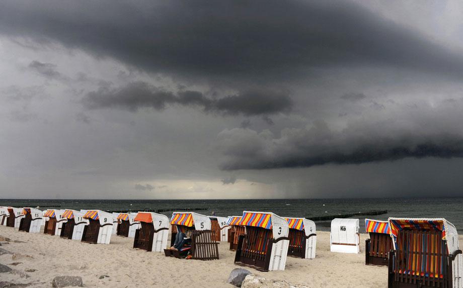 37) Ряды пустых плетеных кресел на пляже возле северо-немецкого города Кюлунгсборн под небом затянутым темными облаками 25 июля 2009. В последнее время погода в Германии представляет собой сочетание солнца и грозы с проливным дождем. (OLIVER LANG/AFP/Getty Images s)