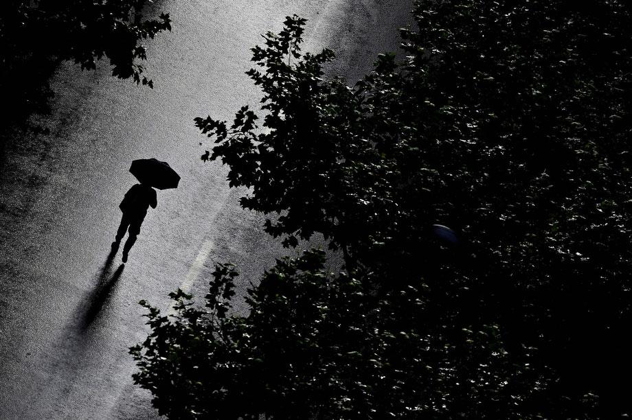 2) Человек идет вдоль улицы после сильной грозы в Шанхае 30 июля 2009. Как сообщили китайские СМИ 30 июля, из-за проливных дождей и оползней с начала июня в южной и центральной части Китая погибли, по меньшей мере, 66 человек и еще 66 считаются пропавшими без вести. (PHILIPPE LOPEZ/AFP/Getty Images)