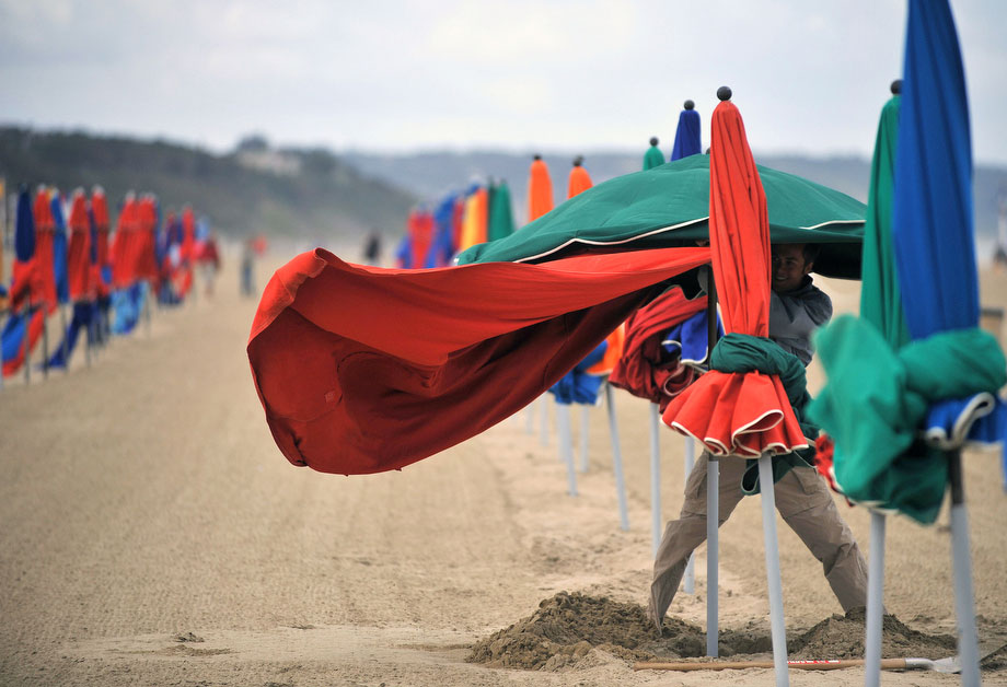 3) Человек пытается открыть пляжный зонтик 30 июля 2009 на пустынном пляже в Довиле, на севере Франции. (MYCHELE DANIAU/AFP/Getty Images)