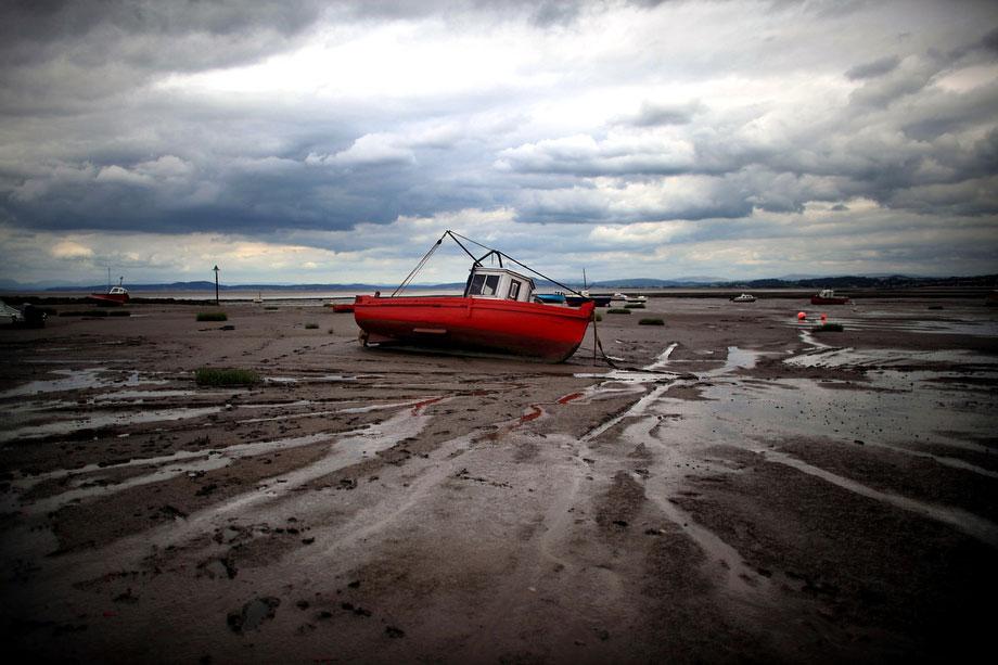 4) Рыболовное судно в песке залива Морокабе под низким серым небом 31 июля 2009 года в английском городе Моркамбе. Многие рыбаки по всей Великобритании терпят убытки из-за неблагоприятных погодных условий. (Photo by Christopher Furlong/Getty Images)