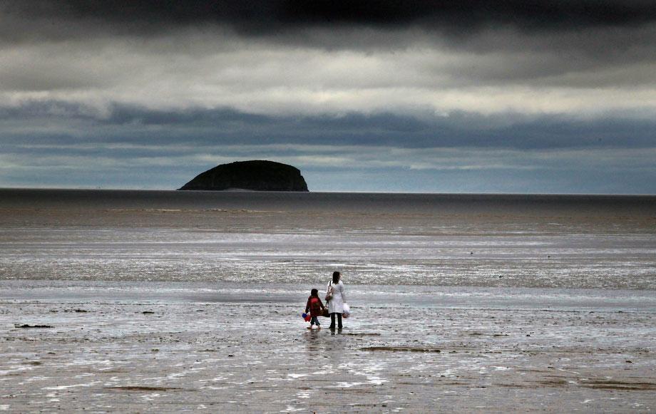 5) Женщина с ребенком на пляже под грозовыми облаками 4 августа 2009 года в Вестон-Супер-Маре, Англия. На многих популярных туристических курортах Великобритании надеются на улучшение погоды и возвращение туристов, которые в этом году предпочитают проводить отпуск у себя дома по причине особенно дождливого лета. (Photo by Matt Cardy/Getty Images)