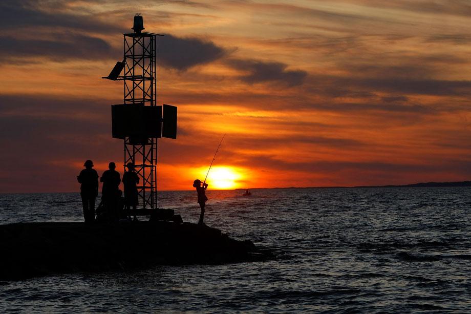 9) Девушки рыбачат на закате солнца 7 августа 2009 года в городе Менемша, штат Массачусетс на острове Марта'c Вайнярд (Виноградник Марты). (Фото: Win McNamee/Getty Images)