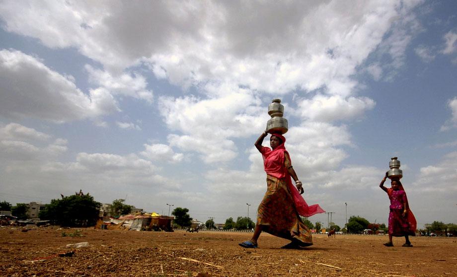 12) Предмуссонные облака над девушками, которые несут воду в Ахмадабаде, Индия, во вторник, 2 июня 2009. (AP Photo/ Ajit Solanki)