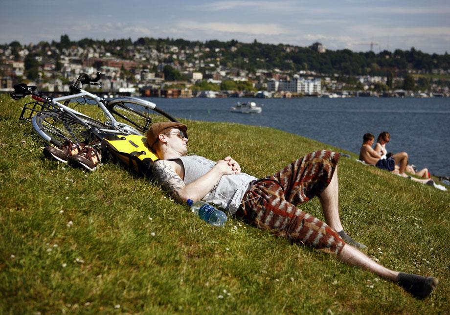 13) Кристиан Джонс из Сиэтла загорает на газоне в парке Газ Воркс 4 июня 2009 года в Сиэтле, на второй день рекордно высокой температуры в этом городе. Джонс говорит, что хотел бы, чтобы такая погода стояла в его городе, знаменитом своими туманами и дождями, каждый день. Рекордно высокая температура составила  89 градусов по Фаренгейту (31,6 по Цельсию), что на один градус выше, чем предыдущий рекорд, зафиксированный в 1989 году. (AP Photo/Seattle Post-Intelligencer, Joshua Trujillo)
