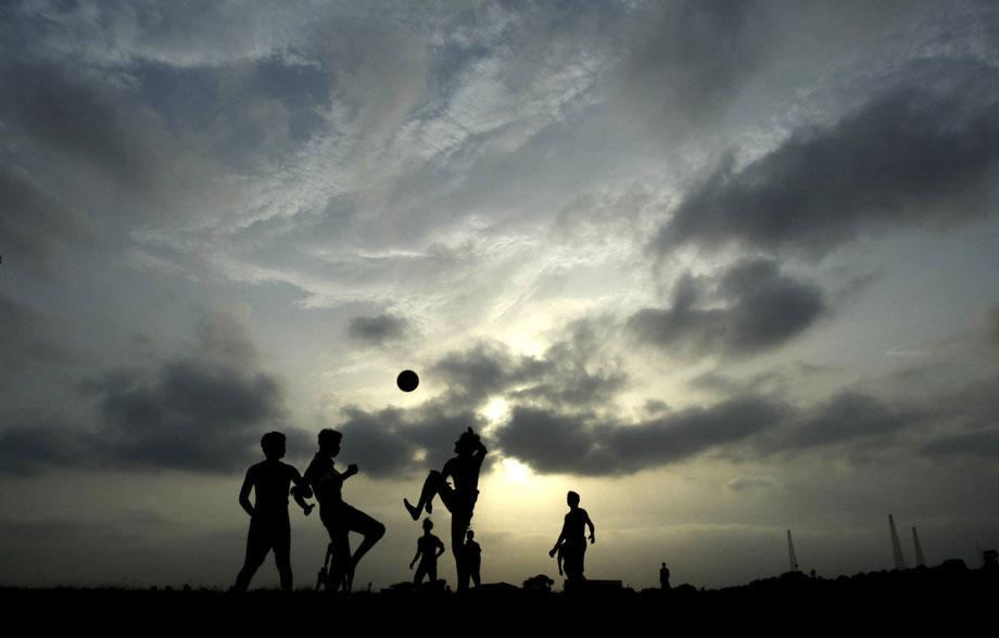 14) Дети играют в футбол под густыми облаками в индийском городе Бхубанешвар, во вторник, 9 июня 2009. (AP Photo/Biswaranjan Rout)