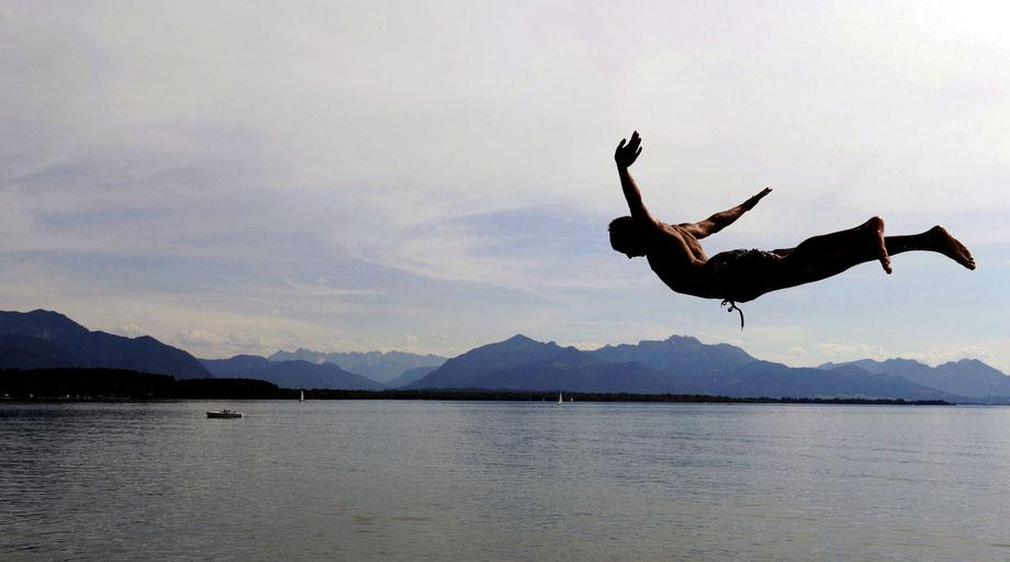 15) Молодой человек прыгает в воды озера Кимзее, расположенного в Альпах вблизи местечка Chieming, в южной части Германии, 14 июня 2009. В этот день стояла солнечная погода, и температура составляла 25 градусов. (AP Photo/Christof Stache)