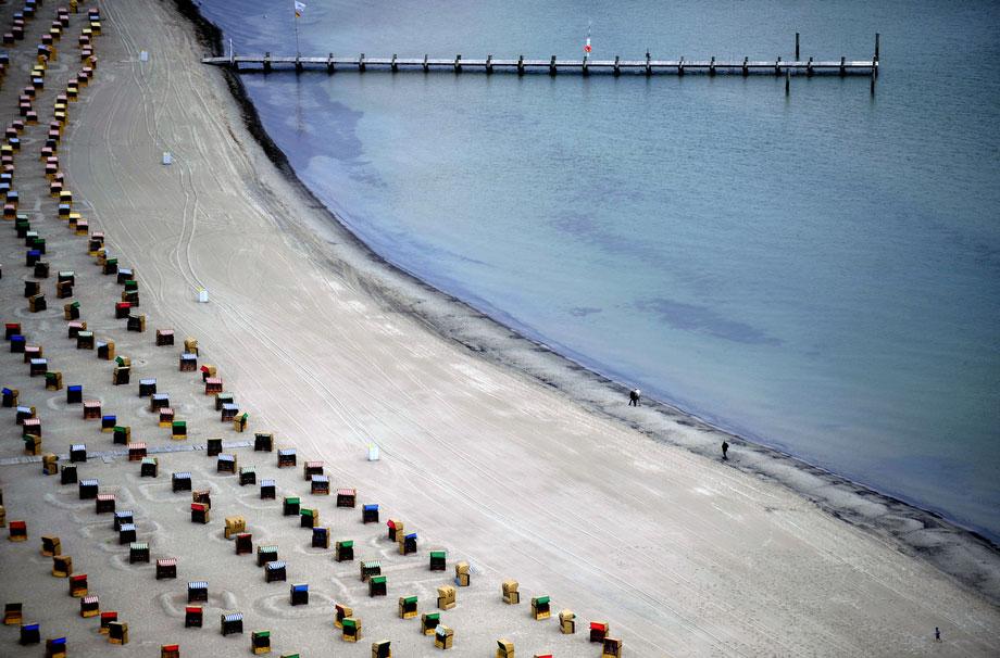 17) Люди гуляют по пляжу рядом с рядами пустых пляжных кресел в пятницу, 19 июня 2009 в немецком курортном городе Травемюнде на Балтийском море. (AP Photo/Fabian Bimmer)