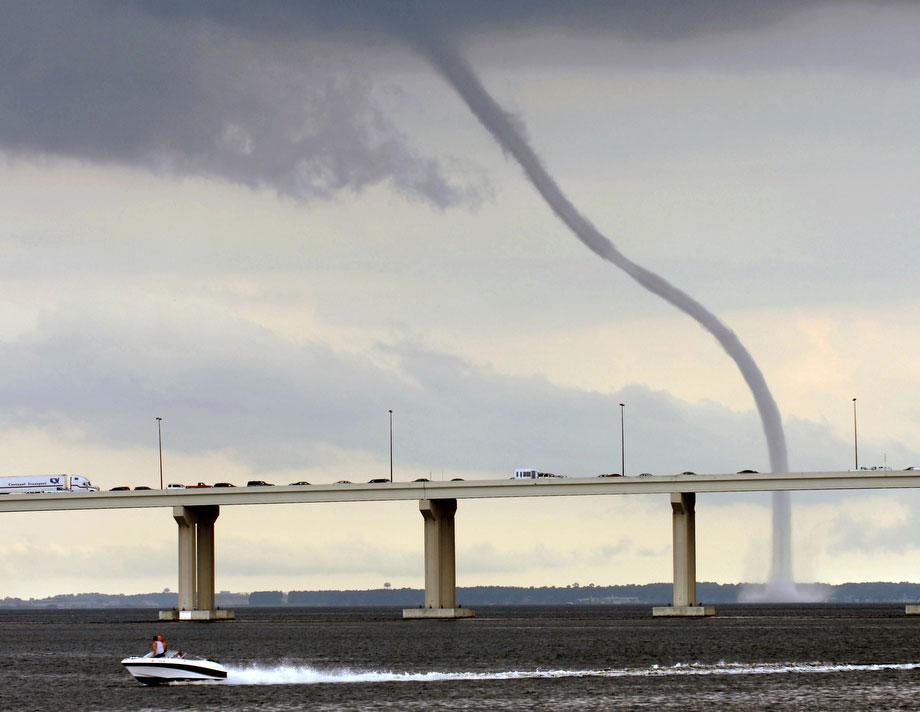 20) Огромный водяной смерч на реке Сент-Джонс в Джексонвилле, штат Флорида в пятницу днем, 26 июня 2009. Достигнув другого берега реки, смерч рассеялся. На переднем плане снимка виден мост Фуллер Уоррен. (AP Photo/The Florida Times-Union, Will Dickey)