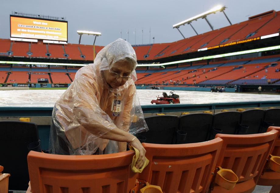 21) Жаннетт Иглстоун вытирает сиденья перед началом бейсбольного матча между командами «Washington Nationals» и «Florida Marlins», который задерживается из-за плохой погоды на стадионе в Майами, 29 июня 2009. (AP Photo/Lynne Sladky)