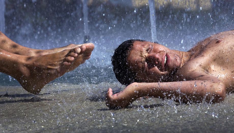 25) Молодежь в прохладном уличном фонтане в Севилье, на юге Испании, 6 июля 2009 года, в день, когда температура почти достигла отметки в 40 градусов. (AP Photo/Miguel Angel Morenatti)