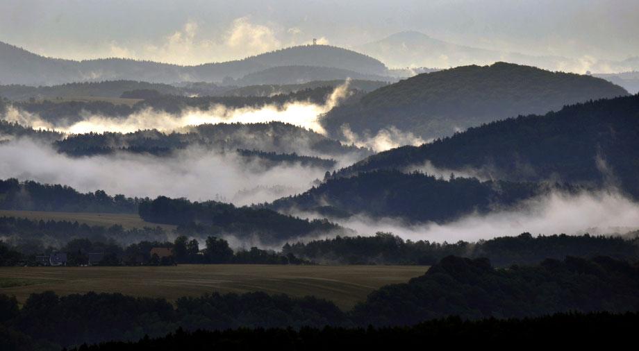 38) Туман в долинах между пиками гор Erzgebirge, во время восхода солнца недалеко от немецкого города Кенингштайн, 8 июля 2009. (AP Photo/Matthias Rietschel)