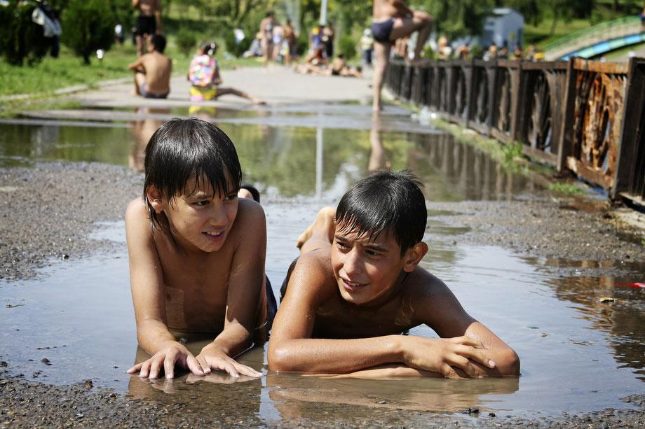 """39) Узбекские дети лежат в луже в Ташкенте, в понедельник, 10 августа 2009 год, в день, когда температура превысила 40 градусов. В июле и начале августа, жители этой страны в Центральной Азии страдают от особенно сильного зноя; этот 40-дневный период жаркой погоды они называют """"саратон"""" или """"чилла"""" (с персидского - """"сорок""""). (AP Photos/Umida Akhmedova)"""