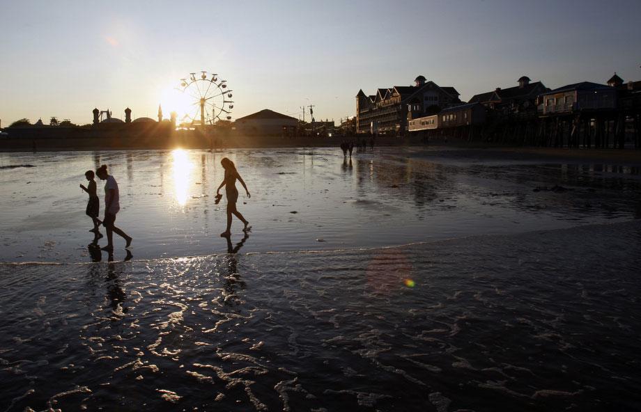 41) Пляжники гуляют по Олд Очард Бич, в штате Мэн, 9 июля 2009. В это регионе в июне почти не прекращались дожди, в результате чего значительно сократился поток туристов, и доходы туристической индустрии в этом году на миллионы долларов меньше, чем обычно. (AP Photo/Robert F. Bukaty)