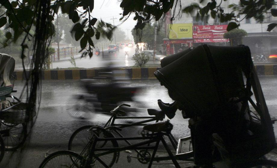 42) Рикша сидит под деревом в своей повозке во время дождя в индийском городе Амритсар, 13 июля 2009. (AP Photo/Altaf Qadri)