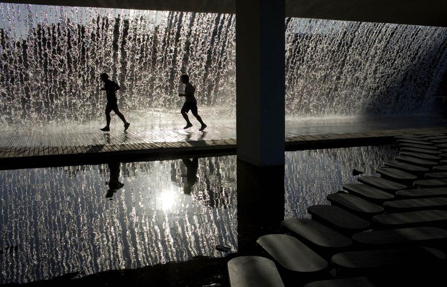 43) Бегуны под фонтаном в Лиссабоне, Португали, 15 июля 2009. Температура в Лиссабоне в ту среду достигла 27 грудусов. (AP Photo/Арманду Franca)