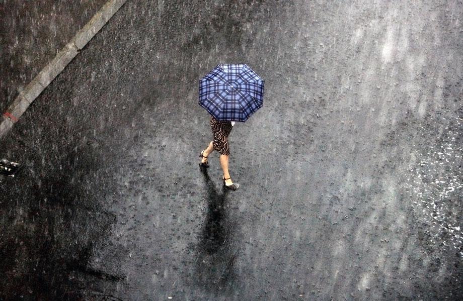 31) Женщина переходит затопленную после грозы улицу в Бухаресте, Румыния, 6 августа 2009. (AP Photo/Vadim Ghirda)