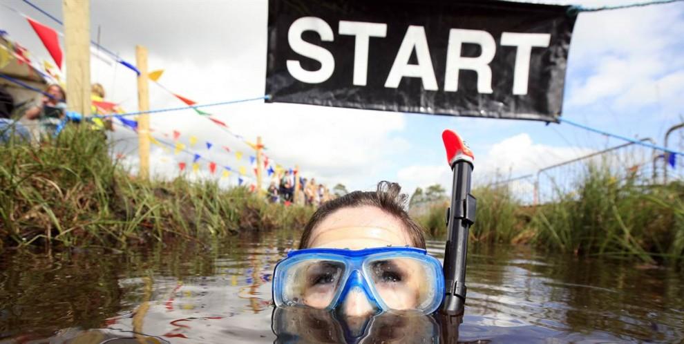 5) Участница чемпионата по плаванию в болоте в Северной Ирландии пересекает линию старта/финиша, парк Питлэндс, Ирландия, 26 июля.