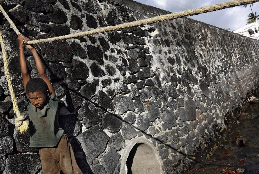 4) Мальчик висит на веревке в старом порту Морони на одном из Коморских островов 3 июля. Коморские острова получили независимость от Франции в 1975 году. С тех пор здесь происходило более 20 государственных переворотов.