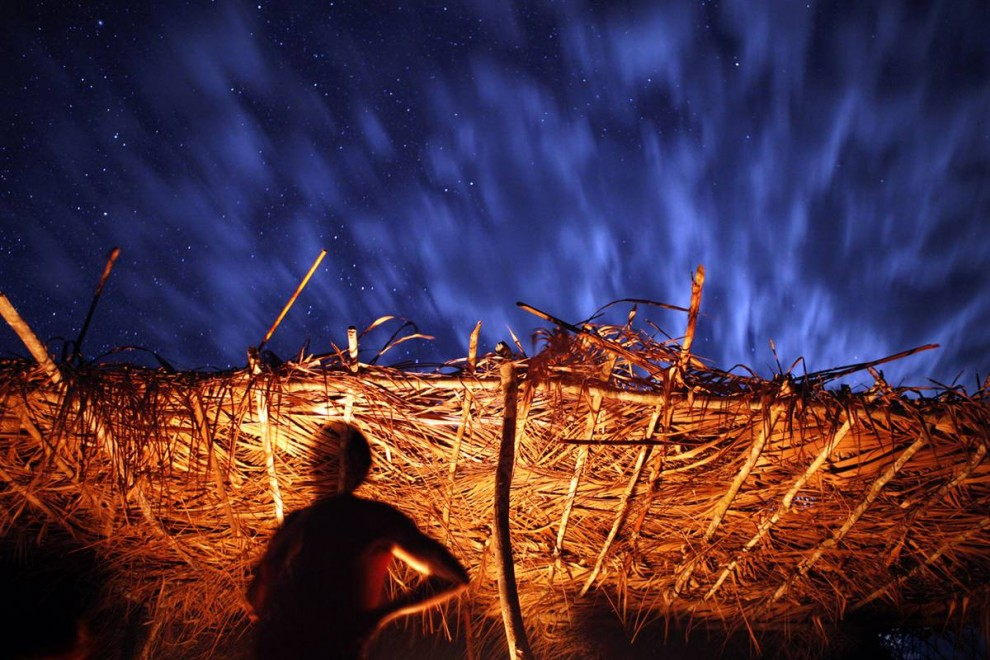 3) Представители народа камаюра собираются вокруг «дома флейты» - священной хижины в центре деревни Мато Гроссо, в которую могут входить только мужчины, Бразилия, июнь. По вечерам старшие жители деревни садятся перед хижиной и курят крепкий табак, обсуждая будущие фестивали, охоту или рыбалку. В этот вечер мужчины камаюра собрались вокруг небольшого костра и под усыпанным звездами небом начали разговор о предстоящем фестивале Явари, на котором воины из деревни соревнуются с воинами из соседнего племени в танцах и ненастоящих битвах.