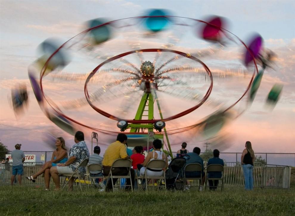 12) Взрослые ждут, пока их дети прокатятся на аттракционе вечером 23 июля, в первый день ярмарки Каньон Каунти в городе Колдвелл, штат Айдахо.