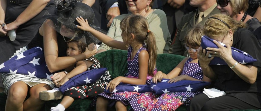 2) Ребекка Л. Балдеозин, слева, обнимает свою двухлетнюю дочь Эмили, а рядом с ней сидят две ее пятилетние дочери-двойняшки, Кайли и Изабелла, на похоронах мужа на национальном кладбище Арлингтона, Вирджиния 4 августа. Муж Ребекки, 30-летний сержант армии США. Хуан К. Балдеозин, из Национальной гвардии Северной Каролины был убит 29 июня в Багдаде после того, как самодельное взрывное устройство взорвалось возле его автомобиля. (Alex Brandon/AP)