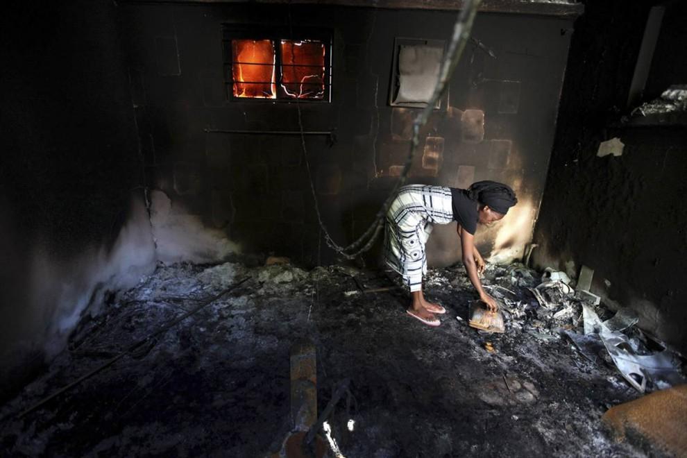 4) Женщина на руинах своего дома, который подожгли исламские боевики. Снимок сделан на севере нигерийского города Майдугури, в 1,2 тысячи км. от столицы страны Лагоса, 3 августа. Более 700 человек были убиты во время восстания радикальной исламской секты на севере Нигерии, которое длилось пять дней. (Akintunde Akinleye/Reuters)