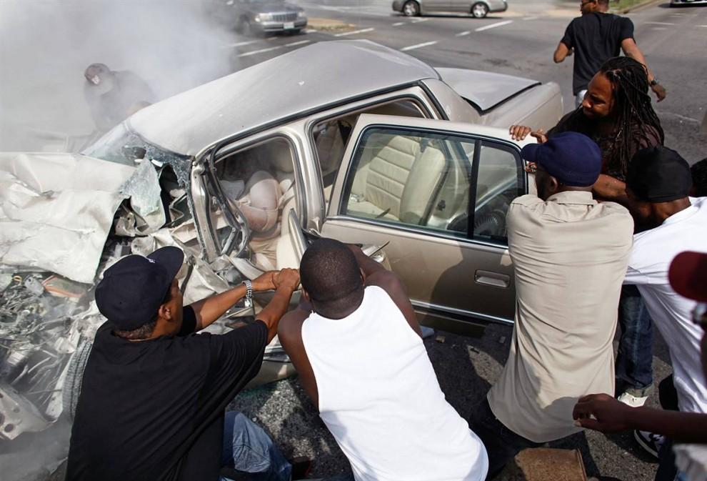 5) Свидетели и добровольцы пытаются снять дверь с машины, пострадавшей в автомобильной аварии 5 августа. Четыре человека получили ранения во время этого несчастного случая произошедшего в Вашингтоне. (Chip Somodevilla/Getty Images)