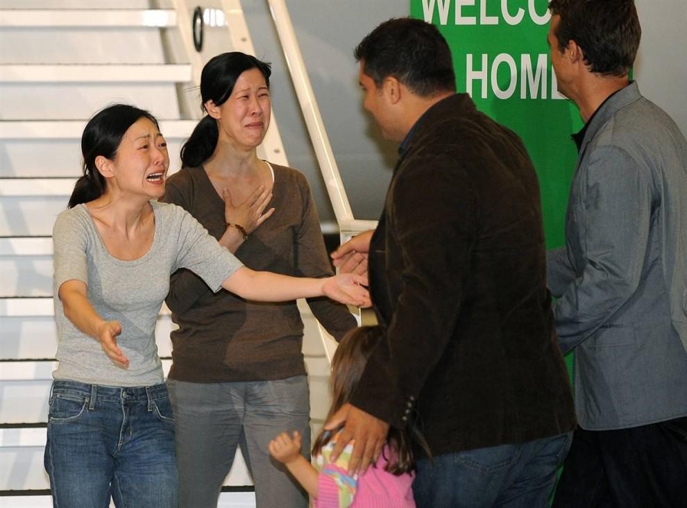 8) Освобожденные американские журналистки: Эуна Ли, слева, во время встречи со своим мужем Майклом Салдате, второй справа, и дочерью Анной, и журналистка Лора Лин, второй слева, со своим мужем Иайном Клейтоном, после прибытия в аэропорт Бербэнк, Калифорния, 5 августа. Две эти женщины в течение пяти месяцев находились в плену в Северной Корее, после того, как нелегально попали на территорию этой тоталитарной страны. Северокорейский лидер Ким Ир Чен помиловал американских журналисток после визита бывшего президента Билла Клинтона. (Robyn Beck/AFP - Getty Images)