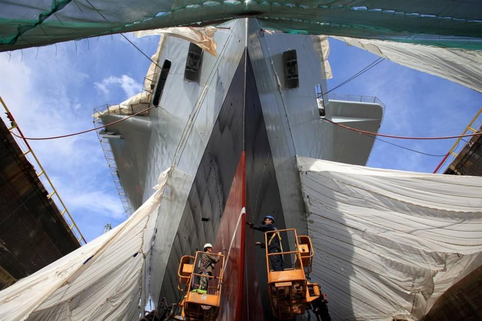 9) Подрядчики красят корпус корабля британских ВМС «Королевский ковчег» (Ark Royal) в сухом доке военно-морской верфи Портсмута 30 июля. Этот флагманский корабль британского флота, легкий авианосец класса Инвинсибл на 20600 тонн, с экипажем более тысячи военнослужащих, находится на службе британских ВМС с 1985 года. Сейчас идет обширное переоборудование корабля, включающее в себя перекраску огромного корпуса специальной краской для уменьшения трения об воду. (Matt Cardy/Getty Images)