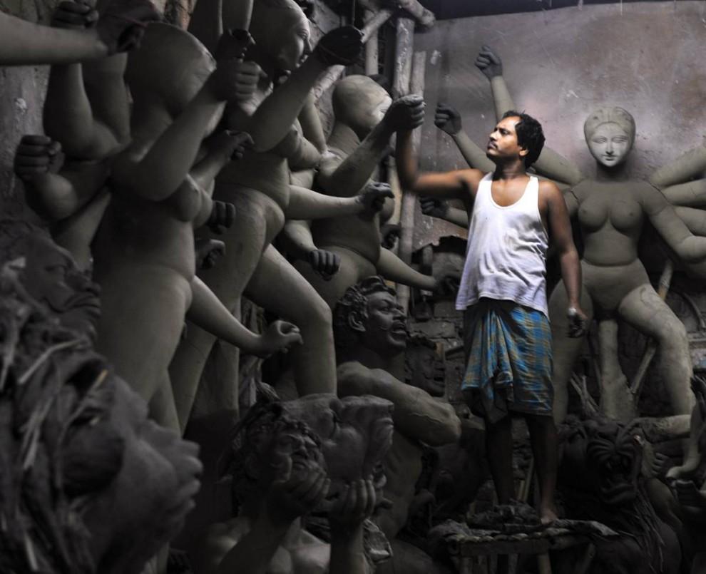 11) Индийский мастер, изготовляющий идолов, работает над глиняной статуей богини Дурги в индийской деревне Кумартули под Калькуттой 30 июля. Согласно местным отчетам, экспорт статуэток из западно-бенгальского района снизился в период кризиса. Глобальный экономический кризис уже ударил по этому бизнесу, и объемы экспортных заказов от иностранных индийцев, принадлежащих к бенгальской общине, сократились. (Deshakalyan Chowdhury/AFP - Getty Images)