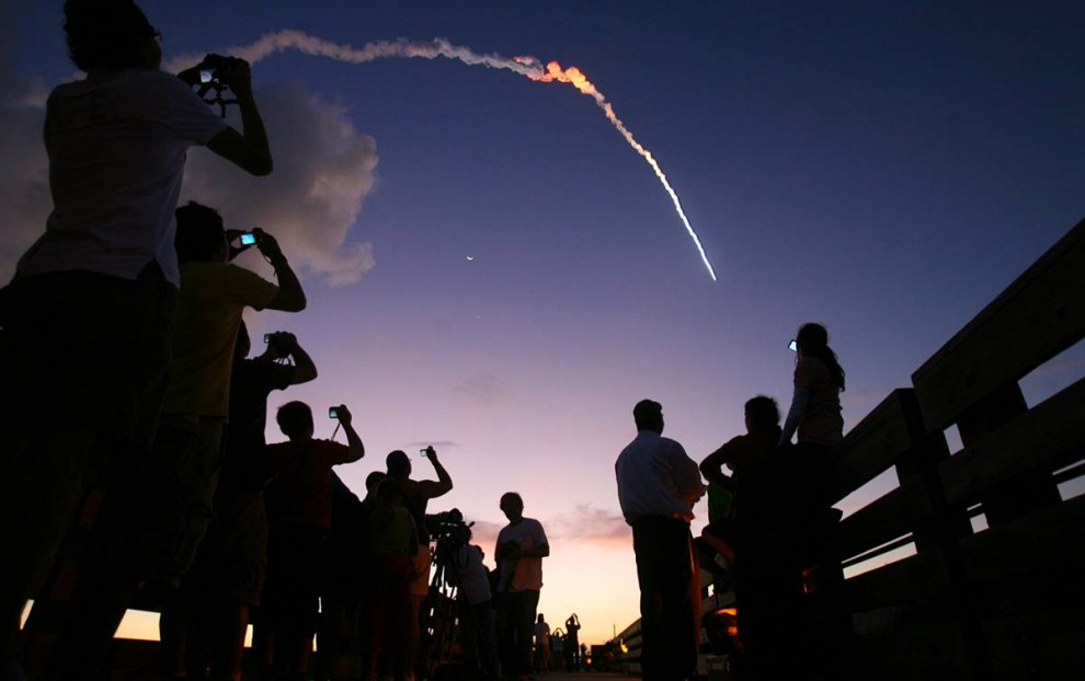 12) Люди, собравшиеся в парке Джетти, фотографируют ракету Дельта 2, во время ее запуска с мыса Канаверал 17 августа. Очередная ракета Дельта 2, несла на себе спутник GPS 2R-21 для его запуска на орбиту. Состоявшийся пуск стал 343-м стартом носителей семейства Delta начиная с 1960 года. (Red Huber/Orlando Sentinel via AP)