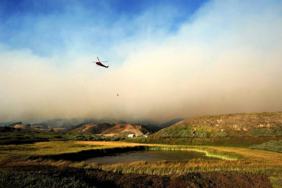 1) Вертолет везет воду, чтоб сбросить ее на горящий лес в районе Санта-Крус Каунти, штат Калифорния. Лесной пожар, расширившийся на более чем в 7200 акров, повредил небольшое число зданий, в основном это были хозяйственные постройки в отдаленных районах. (Noah Berger/AP)