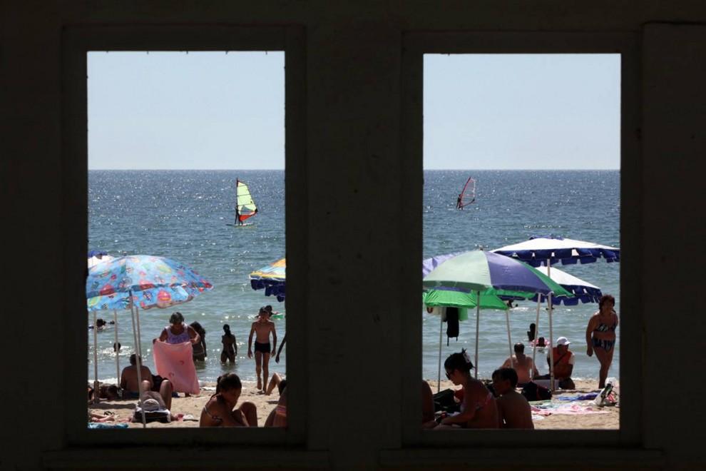5) На этом снимке, сделанном через окна небольшого здания на пляже, видны люди, отдыхающие на берегу Черного моря в районе города Варна, к востоку от болгарской столицы Софии, 13 августа. (Petar Petrov/AP)