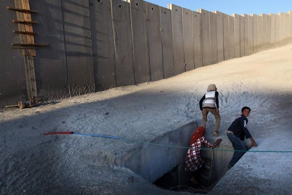 7) Палестинцы выходят из туннеля под одной из частей Израильского разделительного барьера у лагеря беженцев Шуафат на Западном берегу, неподалеку от Иерусалима. Снимок сделан 16 августа. (Pavel Wolberg/EPA)