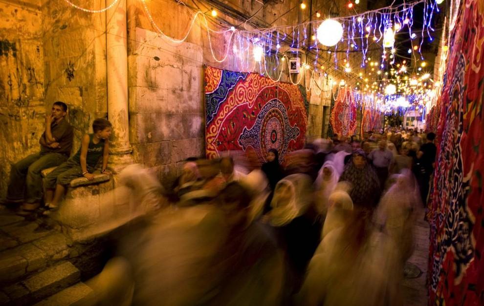 5. Палестинцы смотрят на проходящих людей у мечети Аль Акса, также известной среди евреев как «Храмовая гора», в аллее старой части Иерусалима, украшенной гирляндами в честь священного месяца Рамадан 22 августа. (Sebastian Scheiner / AP)
