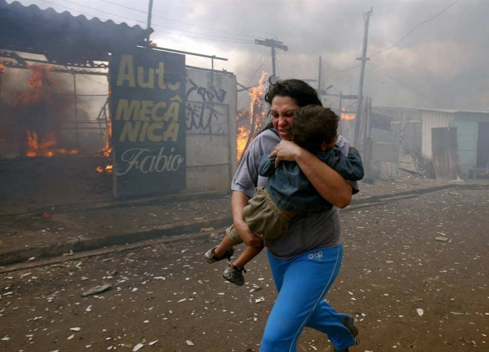 8. Женщина несет ребенка мимо горящего дома в Капао Редондо на окраине Сан-Паулу, Бразилия, 24 августа. Жители начали поджигать дома, чтобы выразить свой протест, после того как полиция и власти выгнали из этих трущоб 800 семей, проживавших здесь нелегально с 2007 года. (Paulo Whitaker / Reuters)
