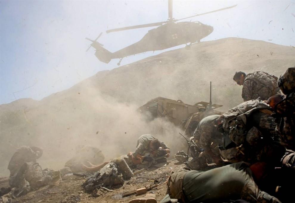 11. 22-летний солдат Пол Пикет из Миндена, Лос-Анджелес, (в центре) из второго батальона 87-ой пехоты третьей военной бригады прикрывает раненого солдата, пока рядом приземляется вертолет, чтобы эвакуировать раненых 19 августа. Их военный бронетранспортер наехал на мину в долине Танги, афганской провинции Вардак. (David Goldman / AP)