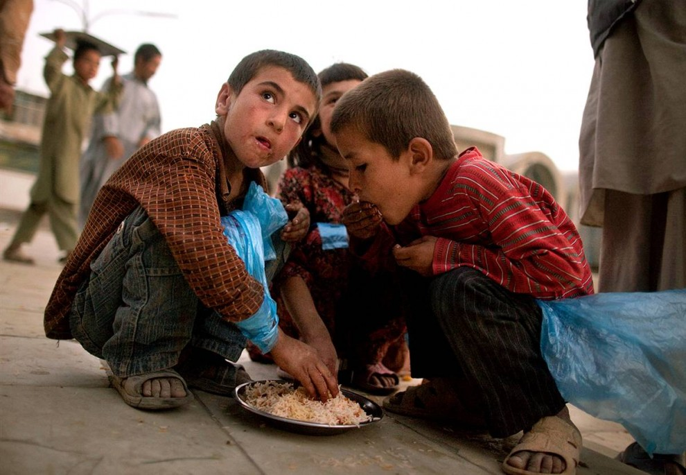 12. Афганские дети едят бесплатную еду на улице у мечети в первый день Рамадана 22 августа в Кабуле. (Paula Bronstein / Getty Images)