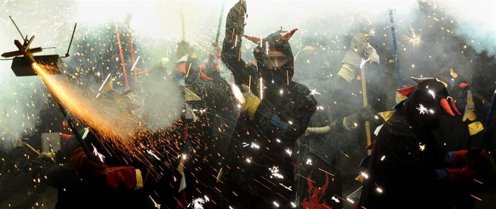 13. Участники фестиваля Коррефок в Барселоне, несут факелы и петарды 21 августа. Слово «коррефок» означает «бег с огнем» и в фестивале принимают участие «дьяволы», играющие с огнем и с людьми. (Manu Fernandez / AP)