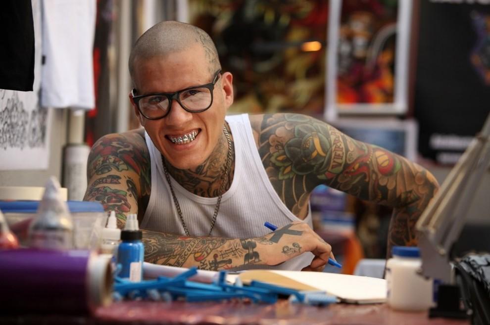 15) Бразильский татуировщик прервался, делая набросок татуировки в день открытия пятого фестиваля тату в Лондоне. (Photo by Oli Scarff/Getty Images)